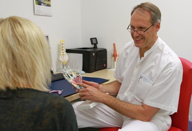 Dr. Engel, Spezialist für Hand- und Fußchirurgie am Krankenhaus Rotthalmünster, erklärt einer Patientin die Anatomie der Hand.