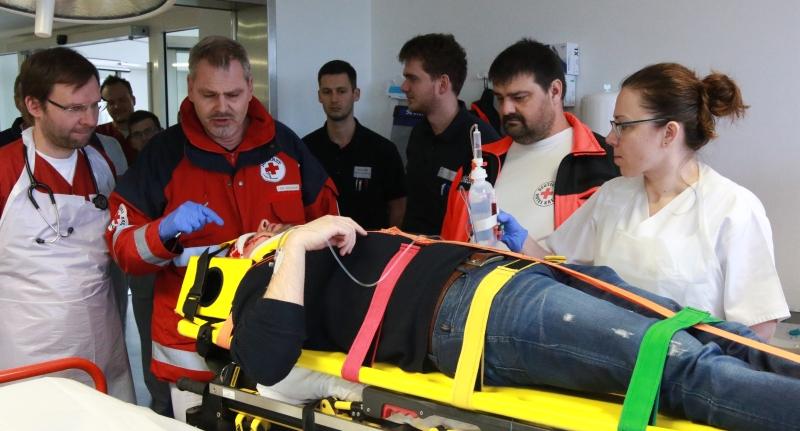 """Übung für den Ernstfall: Notarzt Dr. Stuchlik informiert die Schulungsteilnehmer im Schockraum des Krankenhauses Vilshofen über die """"Verletzungen"""" des eingelieferten Notfallpatienten."""