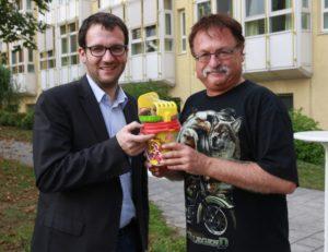 Der Initiator der Aktion, Helmut Dendl (re.), überreicht dem im Juni frisch gebackenen Papa, Bürgermeister Florian Gams, ein Blumenpflanzset für Töchterchen Isabella Luisa.