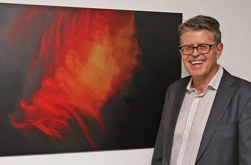 """Chefarzt Dr. Michael Zitzelsberger vor einem seiner ausgestellten Werke: """"Der Feuermensch""""."""