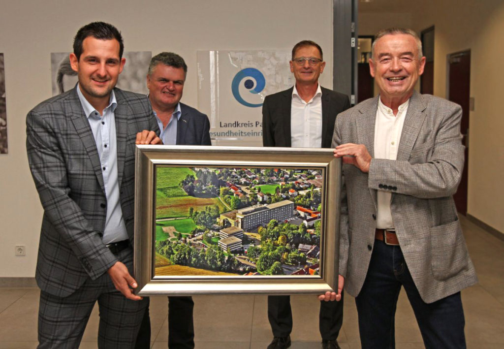 Verwaltungsleiter Florian Pletz (l.) schenkt seinem Vorgänger Peter Baumgartner (r.) ein Erinnerungsbild vom Krankenhaus Rotthalmünster. Die Geschäftsführer Klaus Seitzinger (h. l.) und Josef Mader freuen sich über die gelungene Aufgabenübertragung.