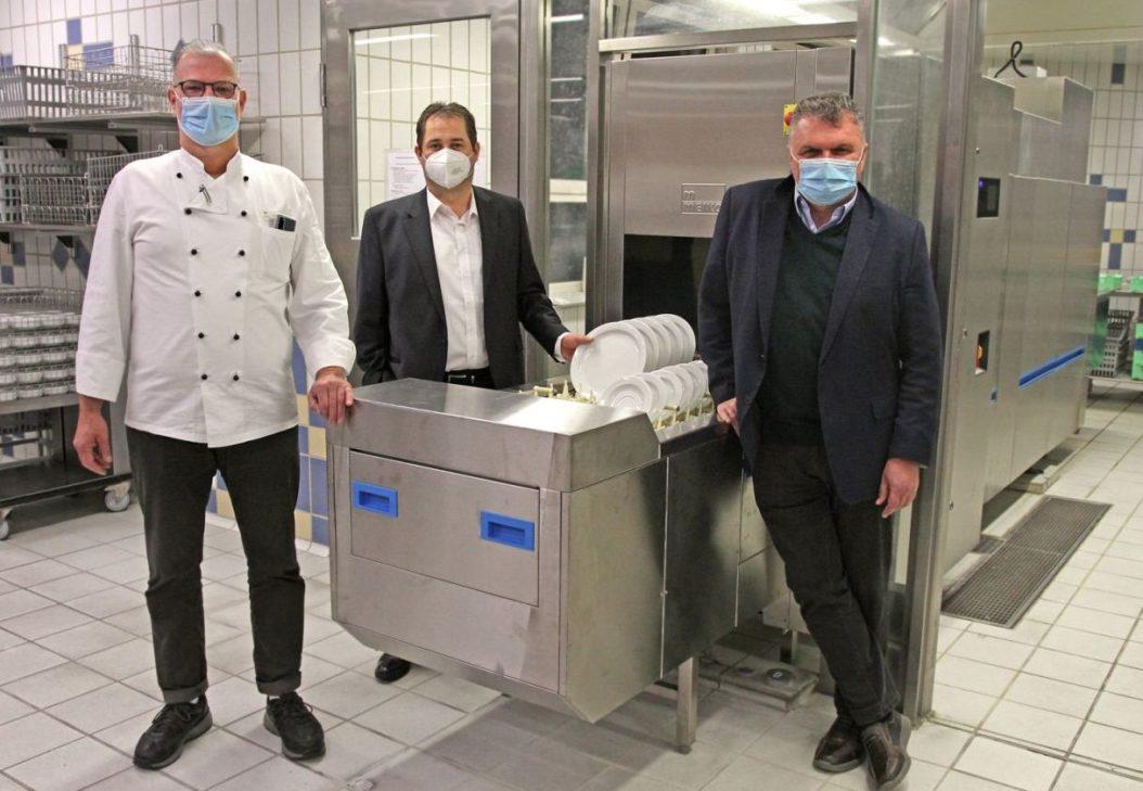 Regional Küchenleiter Karl-Heinz Zuck (v.l.), Verwaltungsleiter Alexander Dötter und Geschäftsführer Klaus Seitzinger vor dem neuen Spülsystem.